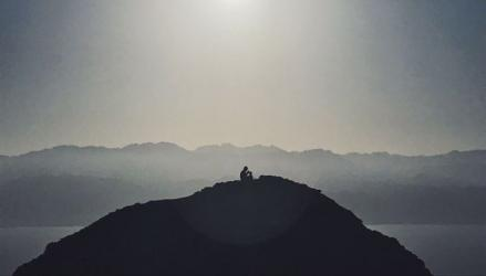 Student photo of a man sitting on a rocky hilltop on a foggy morning